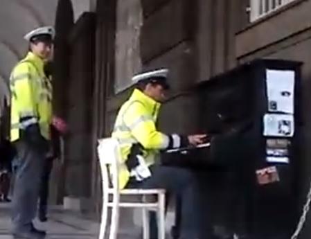 Poliziotto di praga suona il pianoforte in piazza
