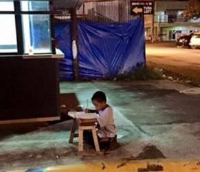 Bambino che fa i compiti alla luce di un lampione: foto simbolo sul web