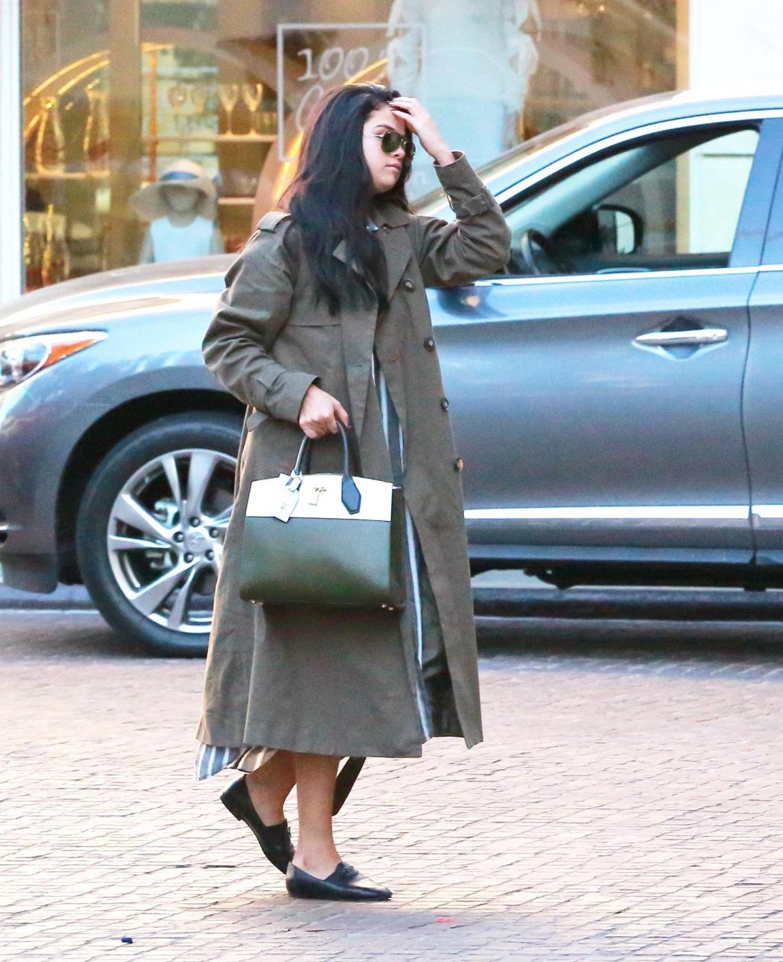 Selena Gomez, trench verde e borsa Louis Vuitton FOTO 1