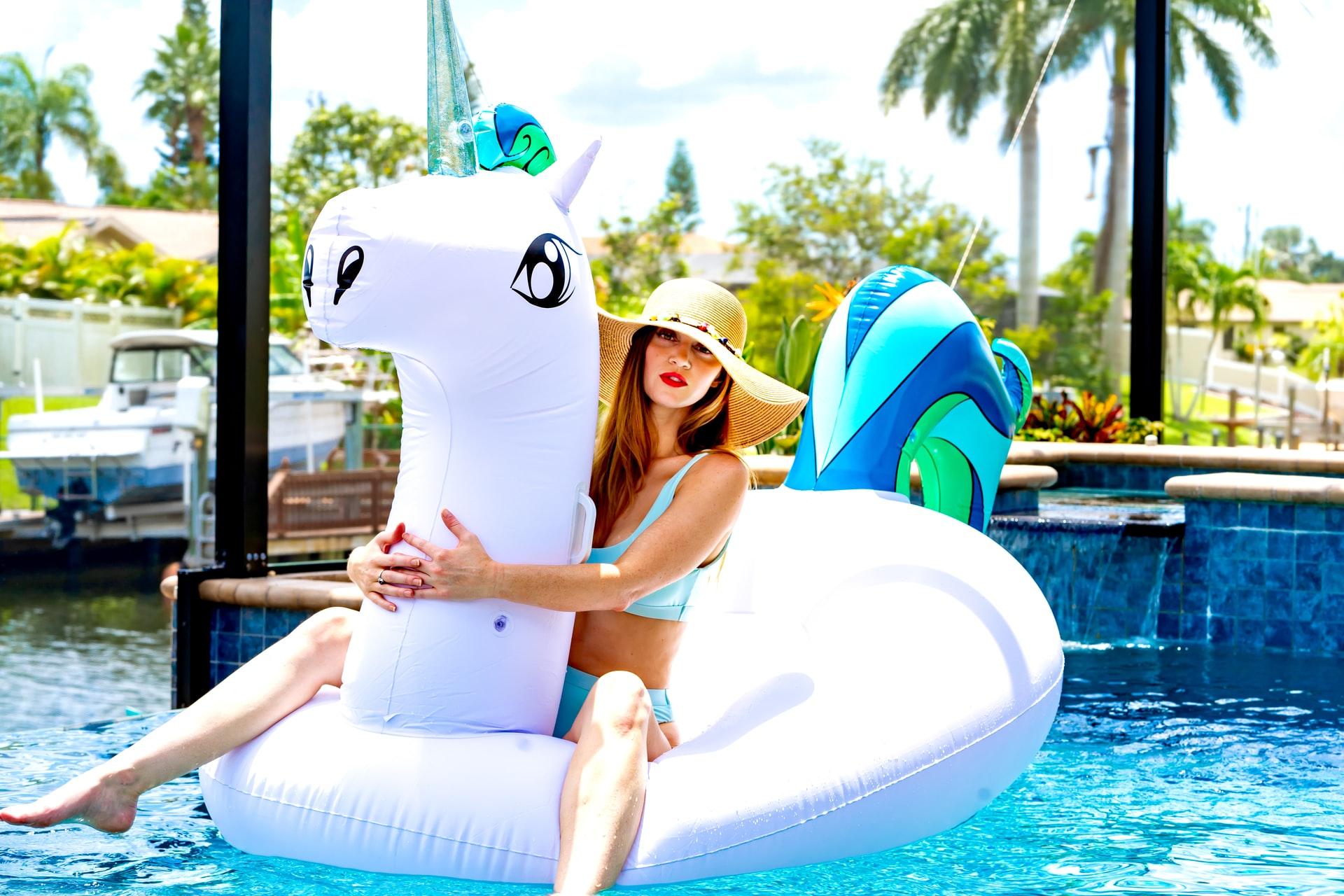 ragazza si diverte in estate sull'unicorno gonfiabile
